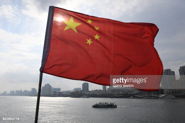 A Chinese tour boat cruises on the Yalu River behind the Chinese flag flying on the Broken Bridge in the border city of Dandong in China's northeast...