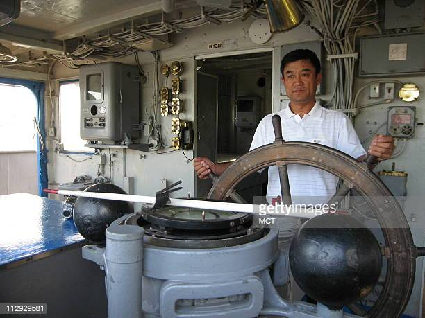 Chinese tourist Han Fuzhu stands at the wheel of the USS Pueblo August 31 a spy ship seized by North Korea in 1968 Some US legislators want to...