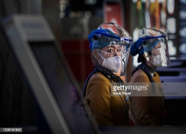 Chinese tourist information clerks wear protective masks and visors as they sit at their desk in the departures area at Beijing Capital International...