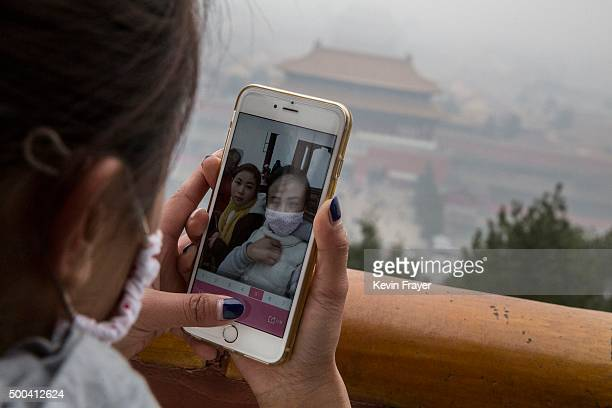 Chinese tourist looks at her phone after taking a picture of herself in a mask while visiting Jingshan Park overlooking the Forbidden City in heavy...