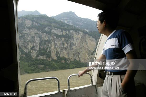 A chinese tourist looks out the window of a Yangtze River boat as he passes by Wu Gorge which is one of the famous three gorges Water levels have...