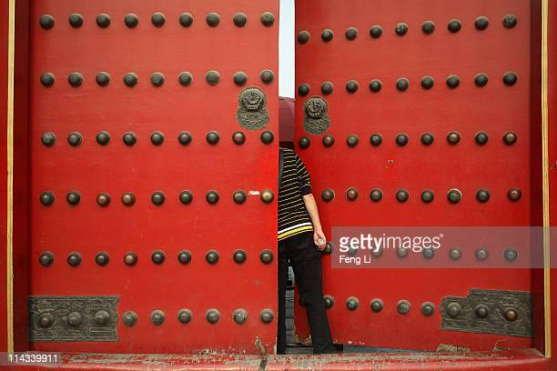 Chinese tourist peeks inside a red door of the Palace Museum inside the Forbidden City which was the Chinese imperial palace from the midMing Dynasty...