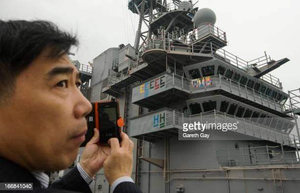 Hong Hong APRIL 16 A Chinese tourist photograph the USS Peleliu during it mooring at Tsim Sha Tsui on April 16 2013 in Hong Kong The amphibious...