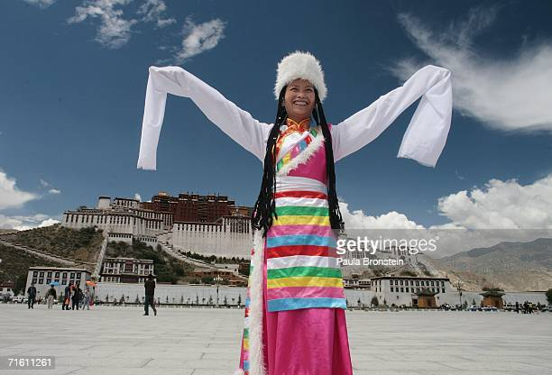 Chinese tourist poses for 2 Yuan wearing a fake Tibetan costume in front of the Potala palace on August 4 2006 in Tibet Autonomous Region China...