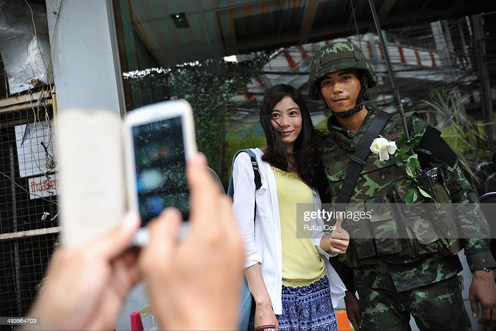 A Chinese tourist poses for a photo with a Thai army soldier standing guard on a city centre street on May 26, 2014 in Bangkok, Thailand. Martial law has been declared across Thailand, with a night time curfew being enforced sporadically, which is having an impact on some street traders and small businesses. Army chief and coup leader General Prayuth has reportedly received royal endorsement after the May 22 coup and has stated his intention to returned stability to Thailand, which has seen months of political unrest and protests that have claimed at least 28 lives.