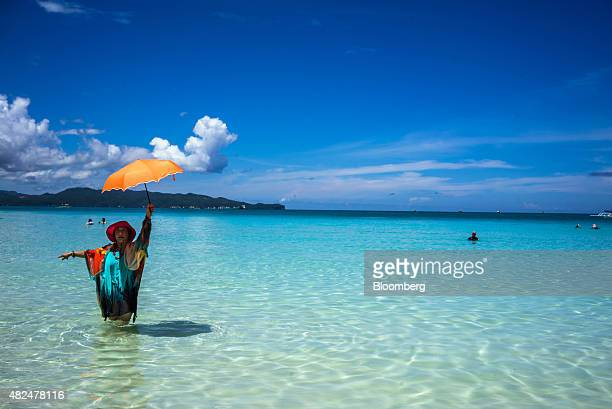 A Chinese tourist poses for a photograph with an umbrella in the sea at White Beach in Boracay the Philippines on Wednesday July 29 2015 The...