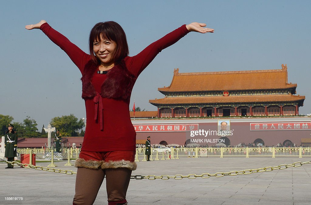 A Chinese tourist poses for photos in Tiananmen Square in Beijing on November 6, 2012. The heirs of Mao Zedong convene this week to anoint China's next leaders, as the Communist Party maintains an iron grip on the economic powerhouse despite mounting calls for change in the Internet era. AFP PHOTO/Mark RALSTON
