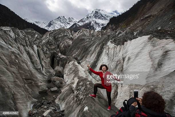 Chinese tourist poses in the tongue of Glacier 1 at the base of the 7556 m Mount Gongga known in Tibetan as Minya Konka on November 13 2015 in...