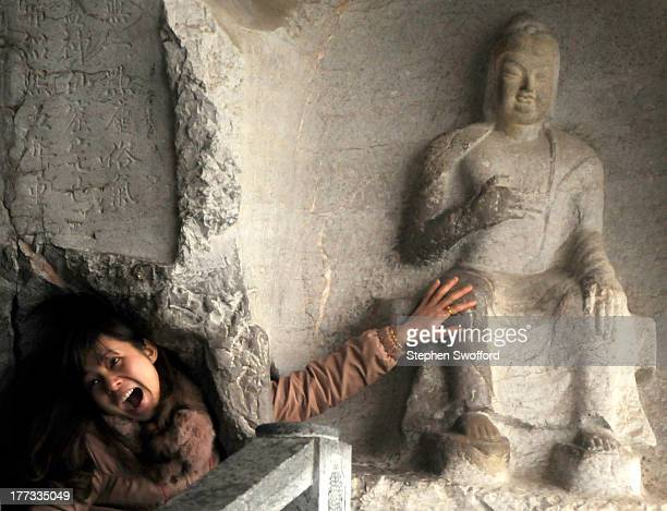 Chinese tourist reaches through a hole in the rock to pet a carving of Buddha in Fubo Hill, Guilin on January 6, 2011.