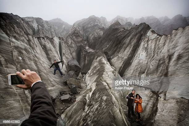 Chinese tourist s pose for pictures in the tongue of Glacier 1 at the base of the 7556 m Mount Gongga known in Tibetan as Minya Konka on November 10...
