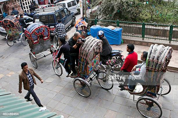 A Chinese tourist takes a photograph of another while riding in rickshaws in the Thamel area of Kathmandu Nepal on Thursday Dec 4 2014 China this...