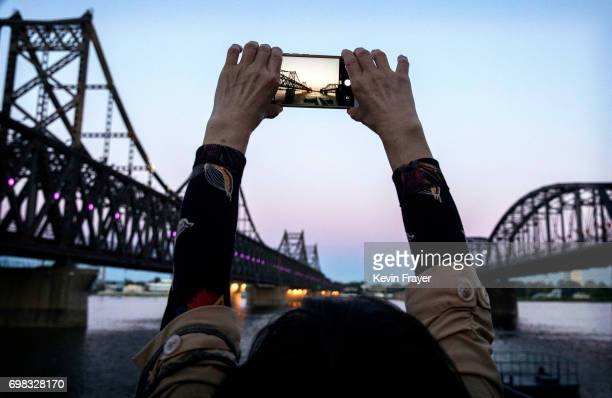 """Chinese tourist takes pictures between """"Friendship Bridge"""", left, and """"Broken Bridge"""", right, as she looks across the Yalu river from the border city..."""