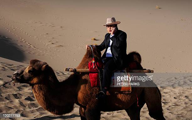 A Chinese tourist talks on his phone while riding a camel through the sand dunes on the outskirts of Dunhuang in China's northwest Gansu province on...