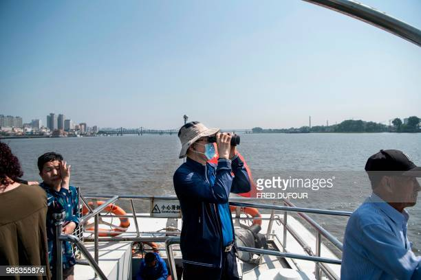 A Chinese tourist uses binoculars to watch the North Korean border on the Yalu river in the Chinese border town of Dandong in China's northeast...