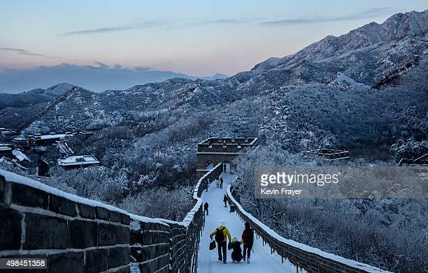 Chinese tourist walk on a slippery section of ice as snow is seen on the Great Wall after a snowfall on November 23 2015 near Beijing China China's...