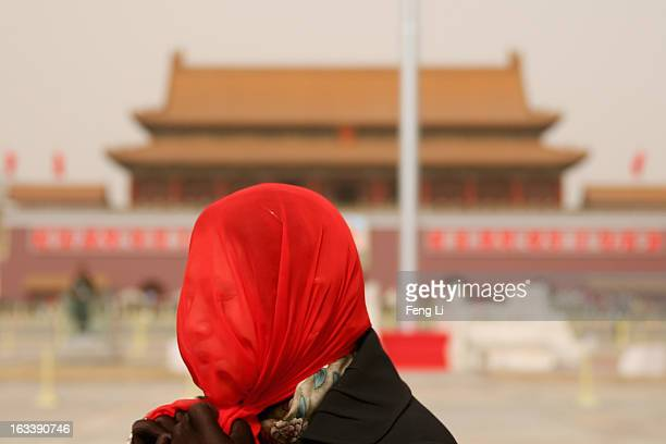 Chinese tourist walks on the Tiananmen Square during the sandstorm on March 9 2013 in Beijing China Strong winds dispersed Beijing's lingering haze...