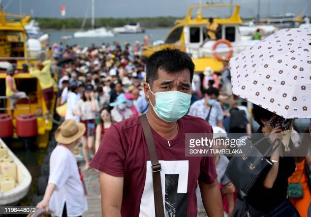 Chinese tourist wearing a facemask as a preventative measure following a coronavirus outbreak which began in the Chinese city of Wuhan, walks after...