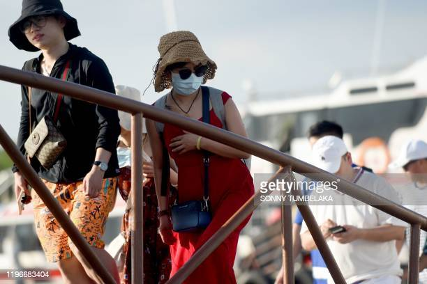 Chinese tourist wearing a facemask as a preventative measure following a coronavirus outbreak which began in the Chinese city of Wuhan, arrives with...