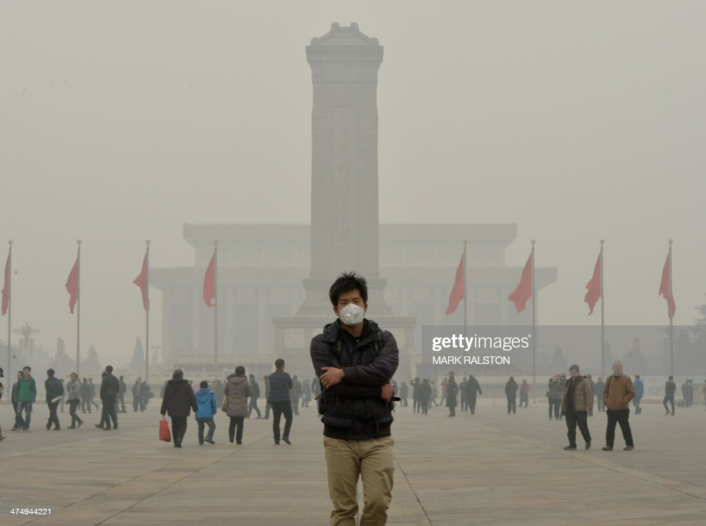 A Chinese tourist wears a face mask in Tiananmen Square as heavy air pollution continues to shroud Beijing on February 26, 2014. Beijing's official reading for PM 2.5, small airborne particles which easily penetrate the lungs and have been linked to hundreds of thousands of premature deaths, stood at 501 micrograms per cubic metre. AFP PHOTO/Mark RALSTON