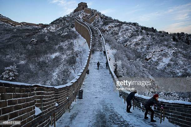 Chinese tourists carefully climb a slippery section of ice as snow is seen on the Great Wall after a snowfall on November 23 2015 near Beijing China...