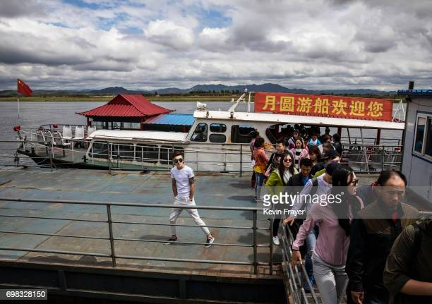 Chinese tourists disembark from a boat on the Yalu river near the border city of Dandong Liaoning province northern China across from the city of...