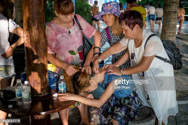 Chinese tourists help out a woman from their group who got fainted from the heat at Vinpearl Land Amusement Park on September 8 2017 in Nha Trang...