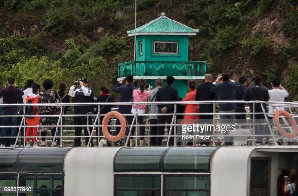 Chinese tourists look and take pictures of a North Korean soldier in a watchtower as they ride on a tourist boat on the Yalu river with North Korean...