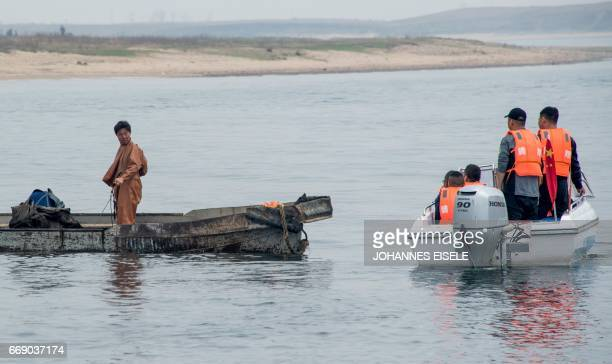Chinese tourists look at a North Korean fisherman on a boat on the Yalu river near Sinuiju, opposite the Chinese border city of Dandong, on April 16,...