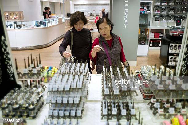 Chinese tourists look at Eiffel Tower souvenir at the Galeries Lafayette shopping center on October 04 2012 in Paris AFP PHOTO / FRED DUFOUR