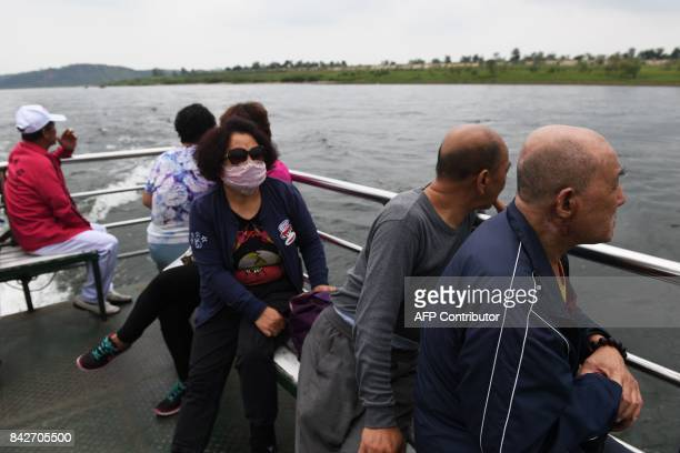 Chinese tourists look out towards North Korea during a cruise on the Yalu river near the North Korean town of Sinuiju opposite the Chinese border...
