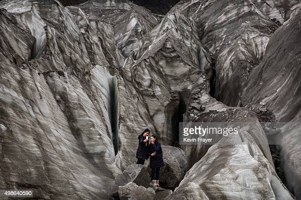 Chinese tourists pose for a picture in the tongue of Glacier 1 at the base of the 7556 m Mount Gongga known in Tibetan as Minya Konka on November 13...