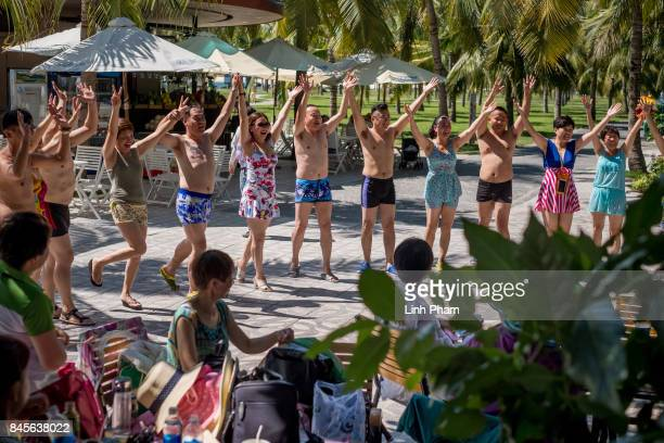 Chinese tourists pose for group photos by the beach of Vinpearl Land Amusement Park on September 8 2017 in Nha Trang Vietnam With a total of 27...