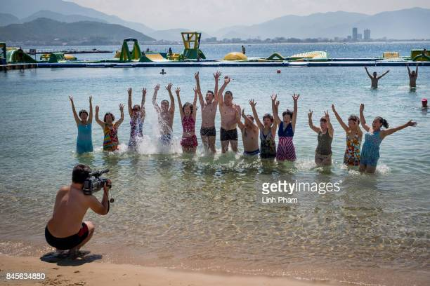 Chinese tourists pose for photos by the beach of Vinpearl Land Amusement Park on September 8 2017 in Nha Trang Vietnam With a total of 27 million...