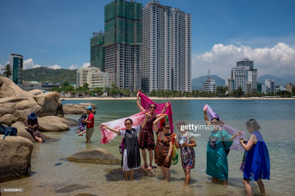 Chinese tourists pose for photos with the rocks at Hon Chong scenic site on September 9, 2017 in Nha Trang, Vietnam. With a total of 2.7 million tourists in 2016, China is Vietnam's largest source of visitors, as most mainland Chinese head to the coastal cities of Da Nang or Nha Trang located in the centre of the country and famed for their beaches, historical sights and seafood. Based on reports, Chinese tour groups have grown to 150 to 200 while the influx has caused problems such as the lack of Chinese speaking staff and inexperience in dealing with inappropriate behavior by the mainland Chinese who have been criticized for their lack of manners in public spaces, including spitting and urinating in public and being noisy at religious places and heritage sites. As Vietnamese travel agencies aim to improve service for Chinese tourists, local media have reported the illegal use of the Renminbi in local markets and Chinese agents and guides acting without proper authorization, leading to distortions in how Vietnam's history and culture have been presented.
