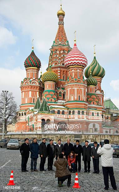 Chinese tourists pose in front of St Basil's church in the center of Moscow on February 29 2012 Russian Prime Minister Vladimir Putin is widely...