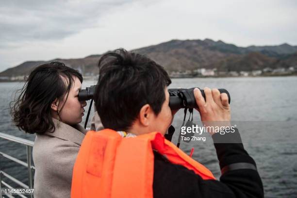 Chinese tourists ride in a boat on the Yalu river with North Korean territory on both sides north of the border city of Dandong, Liaoning province,...