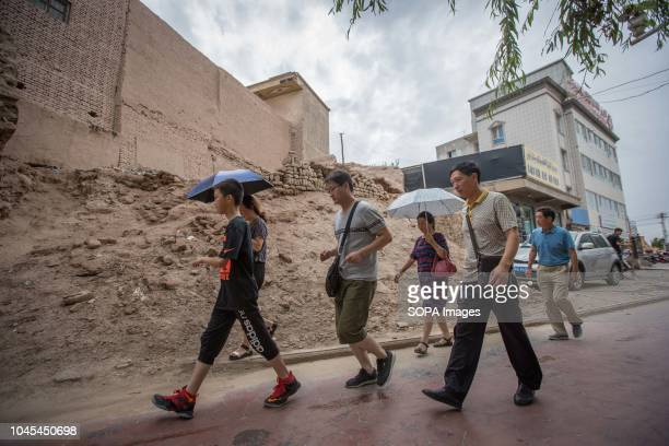 Chinese tourists seen walking next to rubbles of traditional houses set to be completely demolish to make way for new homes in the Kashgar old town...