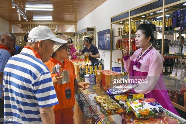Chinese tourists shop at a souvenir store run by the North Korean government in Dandong a Chinese city on the border with North Korea on June 22 2018...