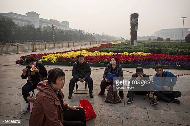 Chinese tourists sit in Tiananmen Square during a polluted morning on October 17 2015 in Beijing China As a result of industry the use of coal and...