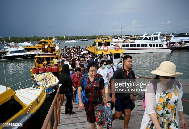 Chinese tourists, some wearing facemasks as a preventative measure following a coronavirus outbreak which began in the Chinese city of Wuhan, walk...