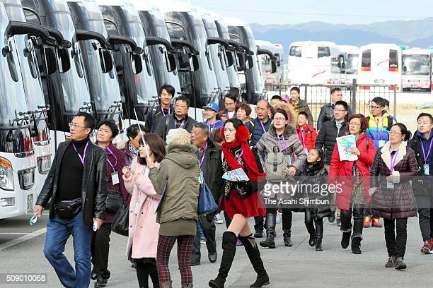 Chinese tourists spending their new year holiday in Japan walk to their buses at a car park after getting off from a cruise ship on February 8 2016...