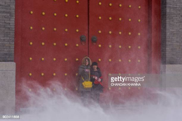 Chinese tourists stand by the gates of the Imperial Palace during a snowfall in Shenyang in China's northeastern Liaoning province on January 8 2018...
