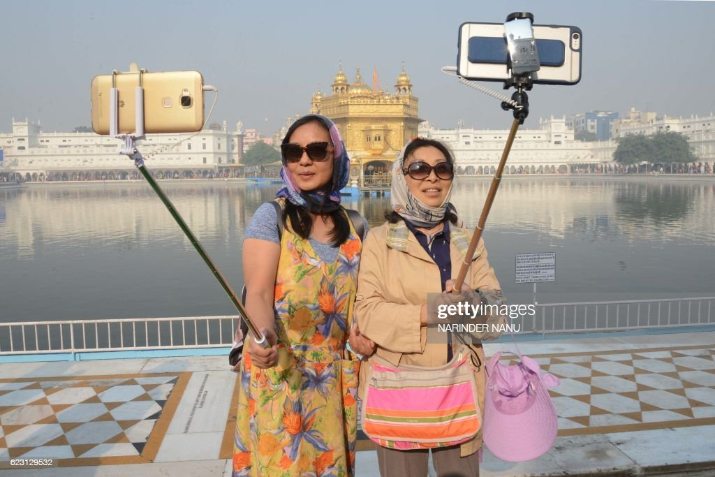 Chinese tourists take a `selfie` at the Golden Temple in Amritsar on November 14 as Sikh devotees mark the 547th birth anniversary of Sri Guru Nanak..