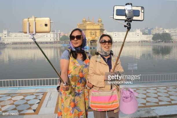 Chinese tourists take a 'selfie' at the Golden Temple in Amritsar on November 14 as Sikh devotees mark the 547th birth anniversary of Sri Guru Nanak...