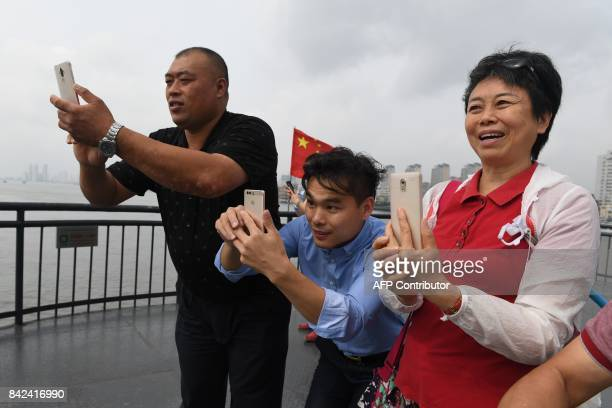 Chinese tourists take photos of North Korea from the Broken Bridge at the Chinese border city of Dandong in China's northeast Liaoning province...