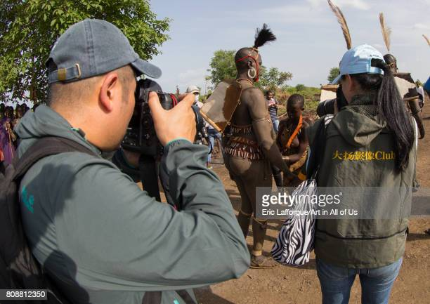 Chinese tourists taking pictures of Bodi tribe fat men during Kael ceremony Omo valley Hana Mursi Ethiopia on June 4 2017 in Hana Mursi Ethiopia