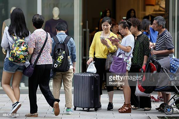 Chinese tourists use smartphones as they stand outside a clothing store in the Ginza district of Tokyo Japan on Sunday Aug 16 2015 Japan's economy...