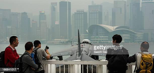 Chinese tourists views aircraft on board the USS Peleliu during its mooring at Tsim Sha Tsui on April 16 2013 in Hong Kong The amphibious assault...