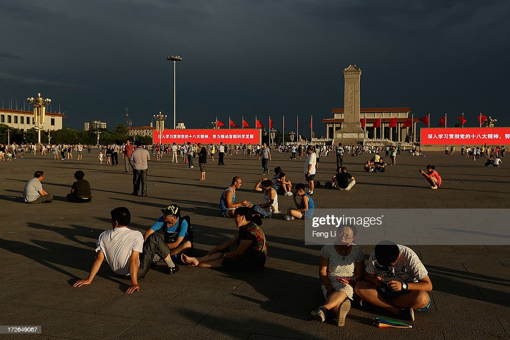 Chinese tourists wait for watching the customary ceremony of lowering flag at Tiananmen Square after several days of heavy air pollution on July 4, 2013 in Beijing, China.