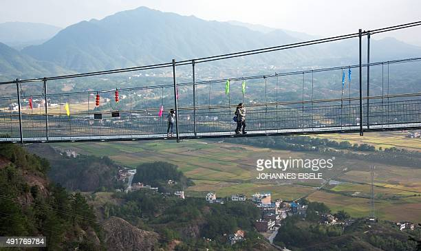 Chinese tourists walk across the glass-bottomed suspension bridge in the Shiniuzhai mountains in Pingjiang county, Hunan province some 150 kilometers...